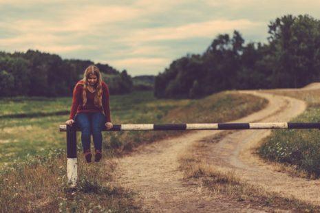 Una niña sentada sobre una valla pensando sobre su aprendizaje