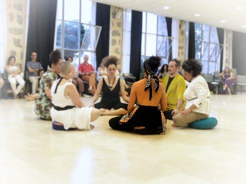 Fin del retiro de meditación. Seis personas sentadas en circulo en postura de meditación.