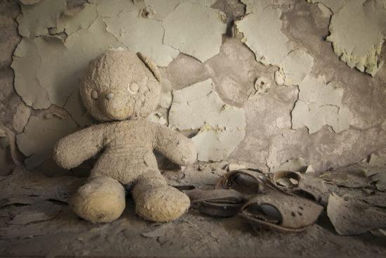 Un peluche abandonado junto a unas sandalias viejas y roidas, símbolo del abandono