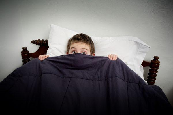 un niño siente a mi viejo amigo, miedo y se tapa con una sábana