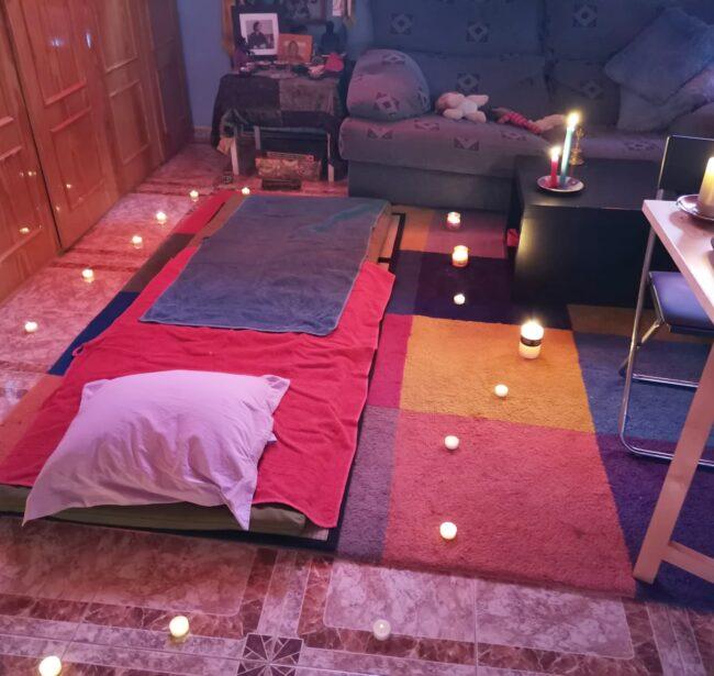 un cojín , un futón improvisado rodeado de velas para el masaje de Ari