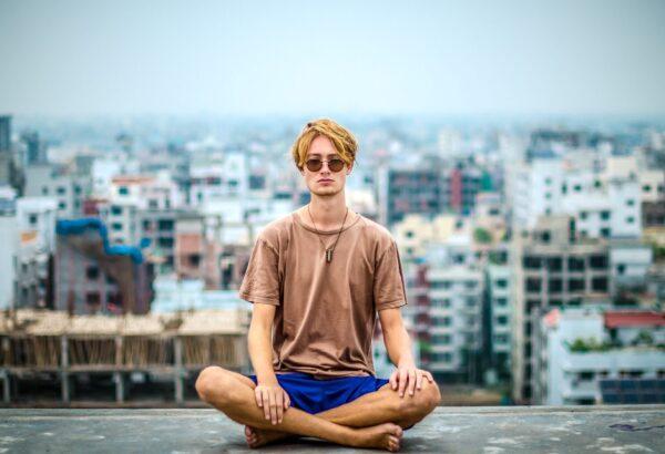 Joven sentado meditando con la ciudad de fondo