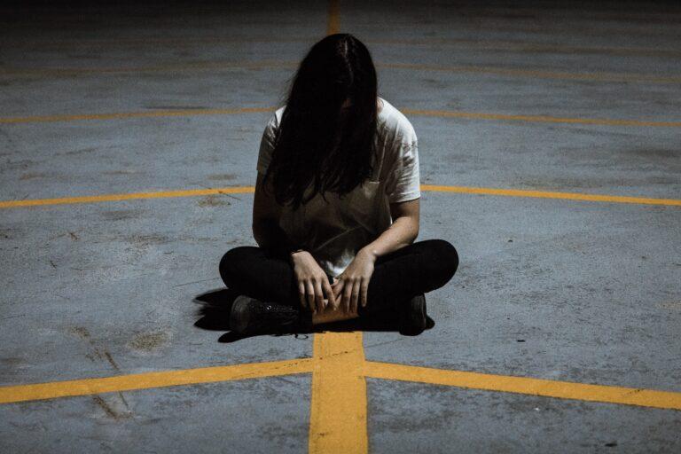 bloqueos emocionales te puede hacer sentir perdido y en una encrucijada. Mujer sentada en el asfalto